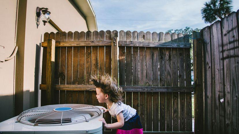 little girl standing over AC fan outside