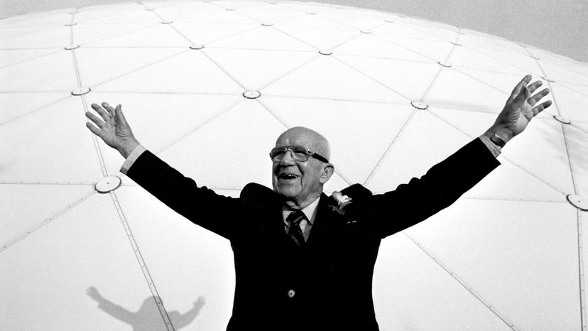 Bucky Fuller standing in front of a giant geodesic dome