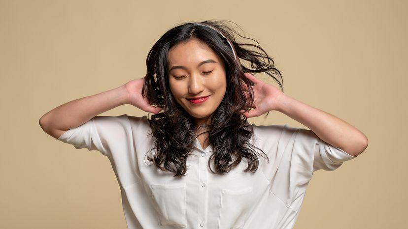 """年轻的亚洲女子听耳机""""width="""