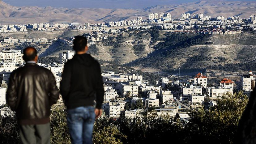 Two men observe the Israeli settlement of Ma'ale Adumim  in the Palestinian West Bank with the Judean desert in the background. THOMAS COEX/AFP/Getty Images