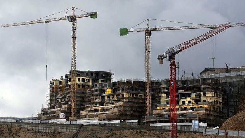 Cranes hover at a construction site in the Israeli settlement of Ramot, built in a suburb of mostly Arab East Jerusalem.  AHMAD GHARABLI/AFP/Getty Images