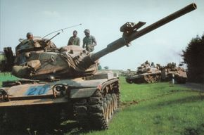 These M-60A1 Main Battle Tanks are on maneuvers. Note the SIMFIRE laser unit mount ahead of the bore evacuator on the main gun.