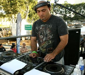 DJs use music mixing software to create loops that can be performed in any order. DJ Nino performs at the Latin Grammy street party.