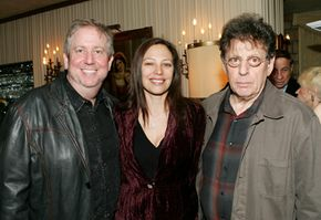 Richard Kraft, left, and Laura Engel, center, of Kraft-Engel Management pose with their client, composer Philip Glass, right.