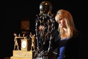 A gallery assistant at London's Bonhams Auction house cleans a French spelter and onyx mystery clock in preparation for a January 2011 sale.