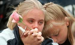 Two teenagers become emotional at a vigil in memory of the Columbine High School shooting victims. Two senior students killed 12 students and one teacher before commiting suicide.