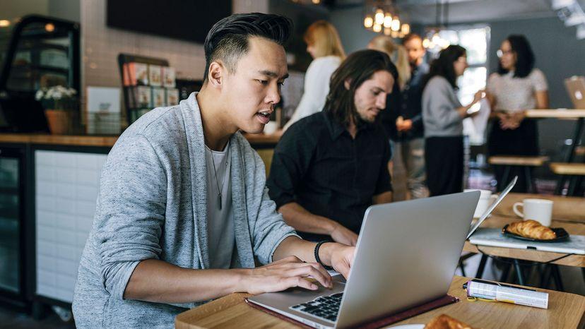 """两个年轻的同事坐在一个繁忙的商务咖啡馆里,边吃边用笔记本电脑工作。""""width="""