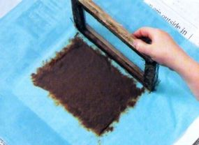 When most of the water has been pressed out, lift the frame away from the pulp. It should stick to the sheet without any holes.