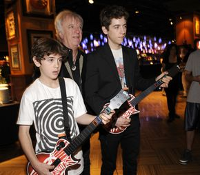 Video games like Guitar Hero offer interactive fun. Brad Whitford, center, checks out Aerosmith Guitar Hero with Harrison Whitford, left, and Graham Whitford, right. See more video game pictures.