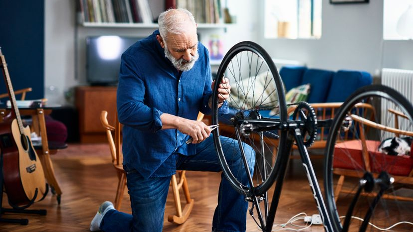 Man in his 50s at home with upside down bicycle repairing it.