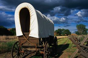 A covered wagon along a wooden fence at the Whitman Mission National Historical Site in Washington state commemorates Marcus and Narcissa Whitman's role in establishing the Oregon Trail.