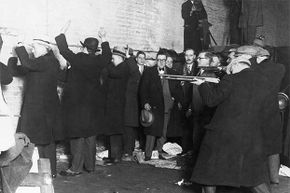 This re-enactment of the St. Valentine's Day Massacre shows the members of Al Capone's gang pretending to be policemen and lining up George Moran's men against the wall to kill them.