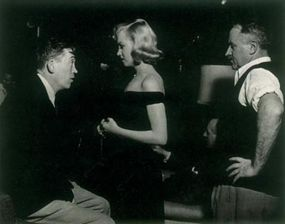 John Huston (left) was one of Hollywood's most thoughtful directors; his films are characteristically vivid and uncompromising. A filmmaker of strict standards, Huston was very pleased with Marilyn's performance in The Asphalt Jungle.