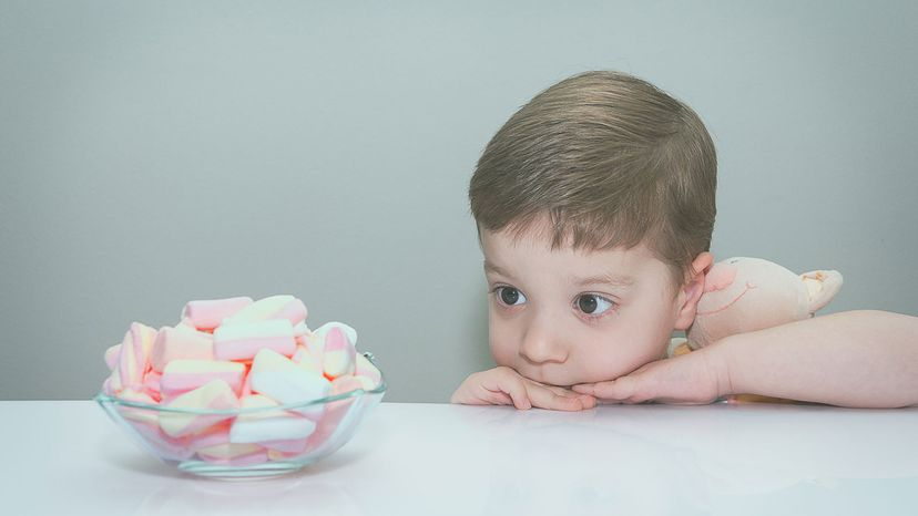 child with bowl of marshmallows