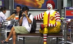 That guy in downtown Singapore isn't eating chicken in a bag. Maybe he wants to keep his hands clean so he can shake Ronald's hand.
