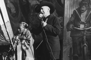 A circus barker promotes a sideshow performer with microcephaly.
