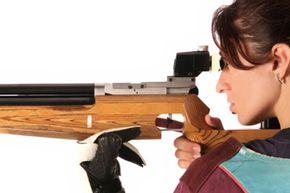 Woman peering down gun barrel