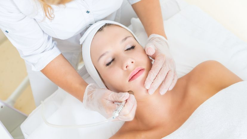Young woman receiving facial microdermabrasion treatment