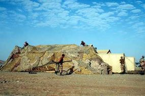 U.S. Air Force airmen concealing a shelter in Operation Desert Shield: The airmen's uniforms, as well as the camouflage net, are designed to blend in with the desert environment.
