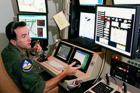 A U.S. Air Force major pilots an MQ-9 Reaper on a training mission from a ground control station.