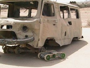 A Packbot Scout searches for booby traps on this truck at Najaf airfield, Iraq, on March 31, 2004.