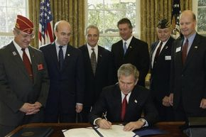 President George W. Bush signs the 2003 Military Family Tax Relief Act on Veterans Day of that same year. The law included a number of tax breaks for military personnel.