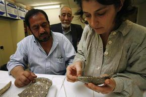 A French restorer assists her Afghan colleagues with reassembling a millefiori discovered in Begram, Afghanistan.