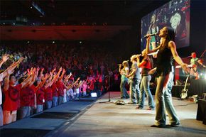 A large crowd raises its hands during a Hillsong Church service in Australia. The church has branches all over the world and attracts thousands of young people.