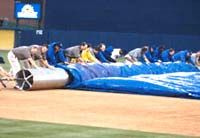 It takes more than a dozen workers to tackle the job of unrolling this huge tarp, which protects the infield from rain.
