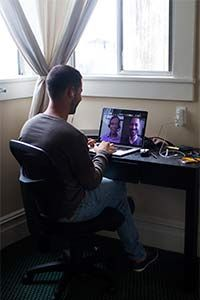A student takes a class from the comfort of his room, using Minerva's proprietary online platform.