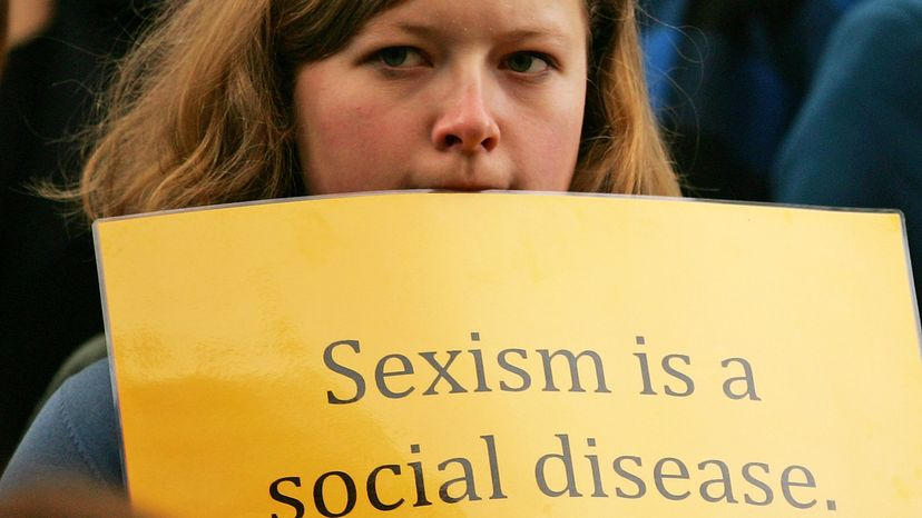 woman holding sexism sign