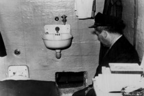 A prison guard kneels by the hole in Frank Morris' cell through which he and John and Clarence Anglin escaped. Prison officials report the hole was dug with broken spoons.