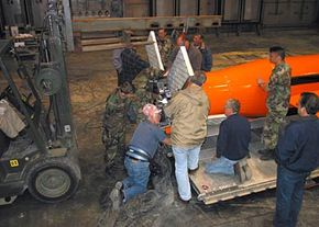 Air Force workers prepare the MOAB for testing. A GPS receiver uses the flaps shown here to change the direction of the bomb as it falls. Smart bombs like this can hit their targets very accurately.