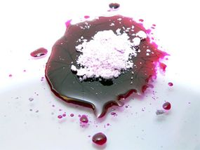 Here, a pile of unrefined dye crystals sits on a pool of activated magenta dye.