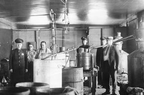 A view of the giant moonshine still taken by the police during a raid in Pittsburgh in 1922. Two of the alleged operators of the still are shown with their coats off. It was one of the largest stills taken since the advent of Prohibition.
