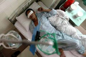 A victim of some poisoned moonshine lies in a hospital in China.