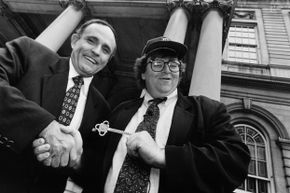 """New York City Mayor Rudolph Giuliani, left, gives the key to the city to filmmaker Michael Moore outside City Hall, during taping of an episode of Moore's NBC television series """"TV Nation"""" in May 1994."""