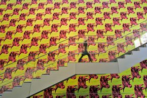 A museum employee walks up a stairway framed by Andy Warhol's cow wallpaper at the Museum of Modern Art in New York. See more pictures of American landmarks.