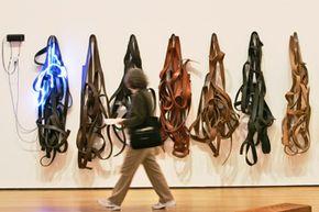 """A visitor at the Museum of Modern Art walks past """"Belts,"""" a Richard Serra sculpture."""