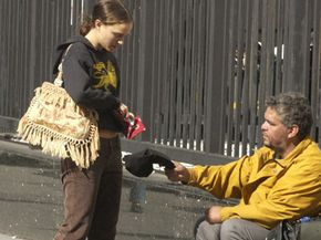 Actress Natalie Portman gives money to a person on the street in 2003 in New York City.