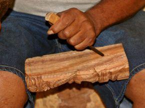 A master wood carver creates a monkeypod wood tiki on the island of Maui in Hawaii.