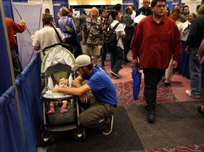 A father tends to his daughter while his wife looks for work at a job fair in Colorado in September 2008, after unemployment hit a seven-year high. See more recession pictures.