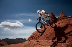 Mountain biking gloves can help riders keep their hands protected during rough rides like this one.