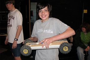 A student at Northfield School of Arts and Technology holds his mousetrap-powered car.