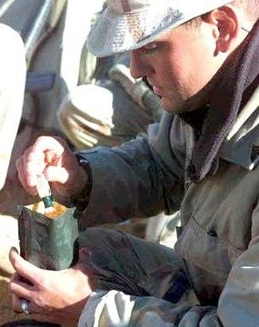 A Marine adds Tabasco sauce to flavor a breakfast MRE
