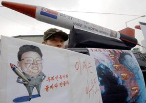 A former South Korean secret commando wearing a North Korean military uniform holds a placard with a caricature of North Korean leader Kim Jong-Il during a demonstration denouncing North Korea's nuclear testing.
