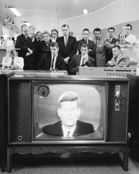 A group of customers in an unidentified store gathers to watch President John F. Kennedy address the nation on the subject of the Cuban Missile Crisis, Oct. 22, 1962.