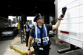 A policeman from the Port Authority of New York and New Jersey uses a radiation detector to check a tractor trailer. The radiation detector will respond to a shipment of batteries, medical X-ray supplies, gases and toxic materials.