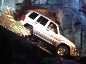 The Jeep Liberty makes a dramatic entrance, driving down a steep, rock-covered incline in front of a waterfall.