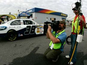 ESPN film crew members capture David Gilliland, driver of the #38 Ford Drive One Ford, leaving the garage area at the beginning of practice for the NASCAR Sprint Cup Series Sylvania 300 at New Hampshire Motor Speedway on Sept. 13, 2008 in Loudon, N.H.